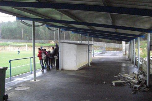 Nenos e nenas xugando mentras ao fondo se ve o muro derrubado do campo de fútbol da Fieiteira